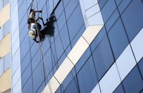مهنة شاقة يقترب العامل فيها من الموت.. تنظيف الزجاج في أحد أبراج مدينة غزة
