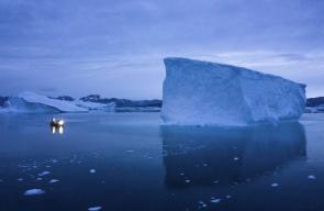 قارب صغير يبحر ليلاً بين الجبال الجليدية الكبيرة شرق جرينلاند
