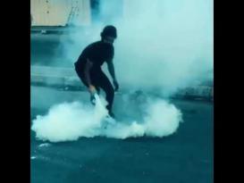 متظاهران يلاعبان قنبلة غاز مسيل للدموع على طريقة لاعبي كرة القدم