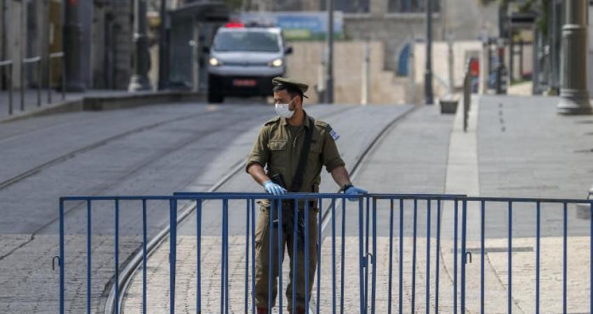 جندي اسرائيلي يقف عند نقطة تفتيش في القدس المحتلة مع انتشار فيروس كورونا