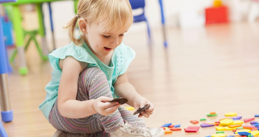 cute-toddler-girl-playing-with-toys-on-daycare-floor-598560038-5be4953746e0fb0026d554b6